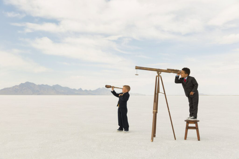 Two young boys dressed in business suits search through telescopes for new business on the Bonneville Salt Flats in Utah. Business teamwork will help you find new places.